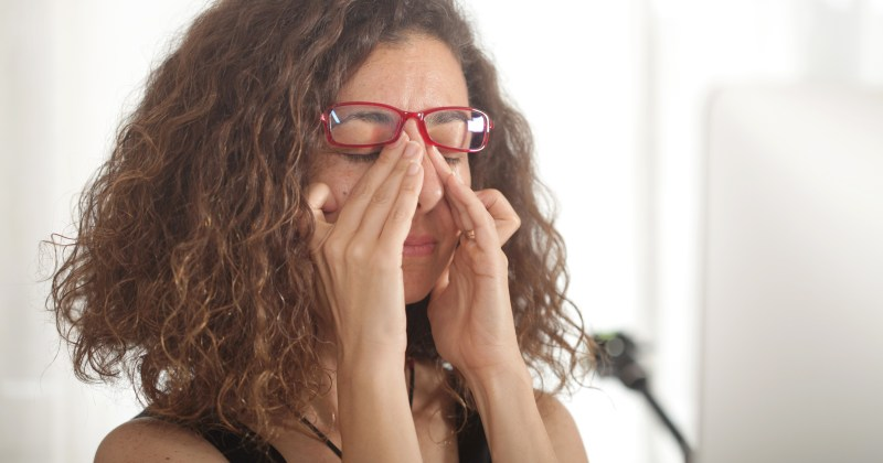 Woman rubbing eyes underneath her glasses