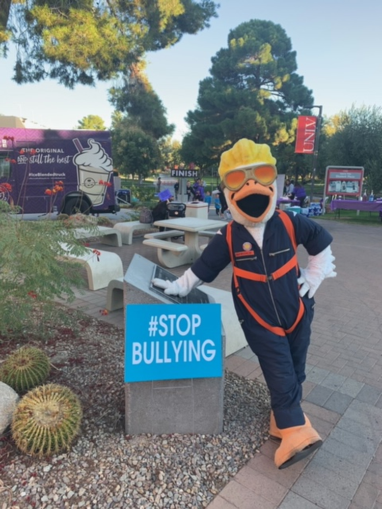 """The mascot fro the Las Vegas Aviators posing in front of a """"#Stop Bullying"""" sign"""