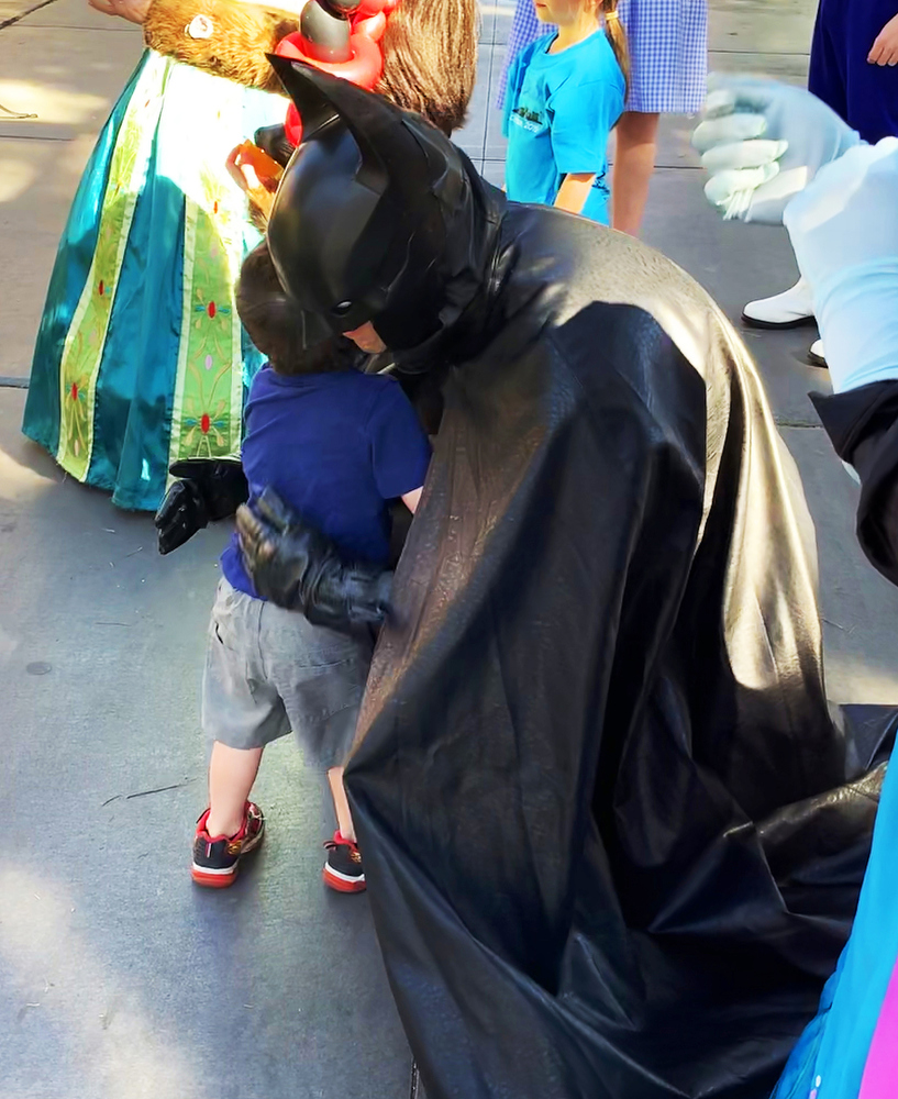 A man dressed as Batman hugging a child