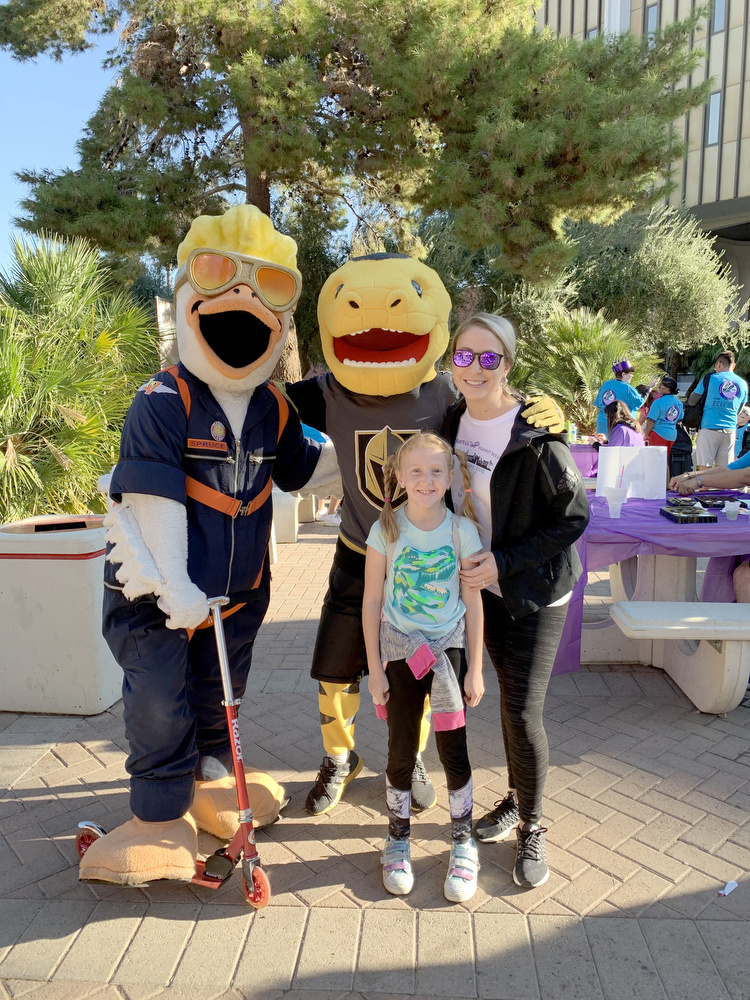 A woman and a child posing for a photo with the mascots for the Las Vegas Aviators, and Golden Knights