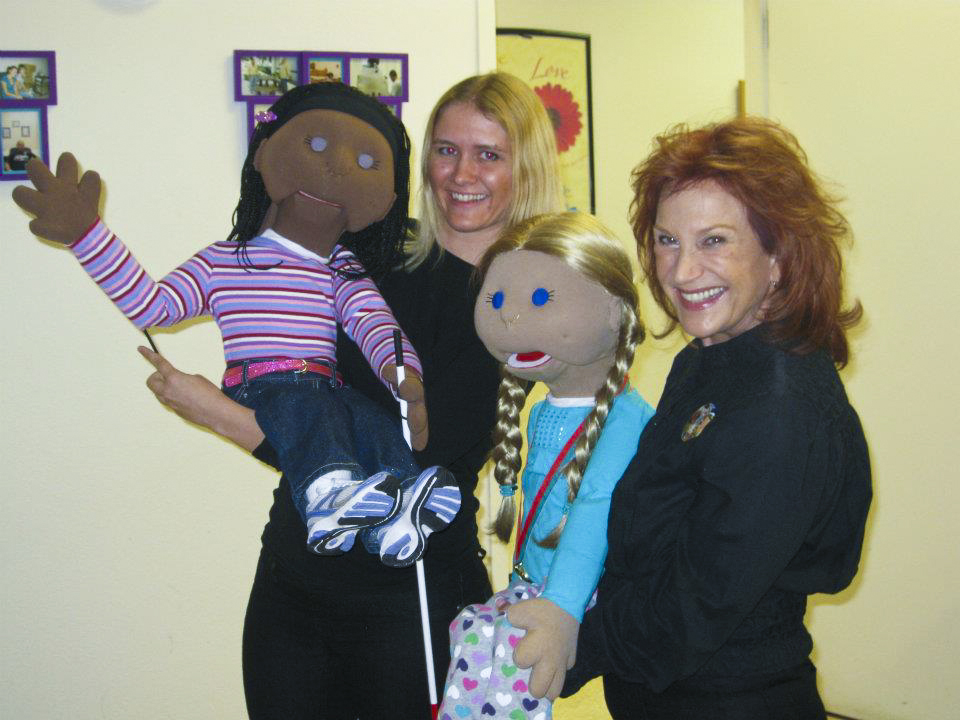 Two people holding Include Me puppets