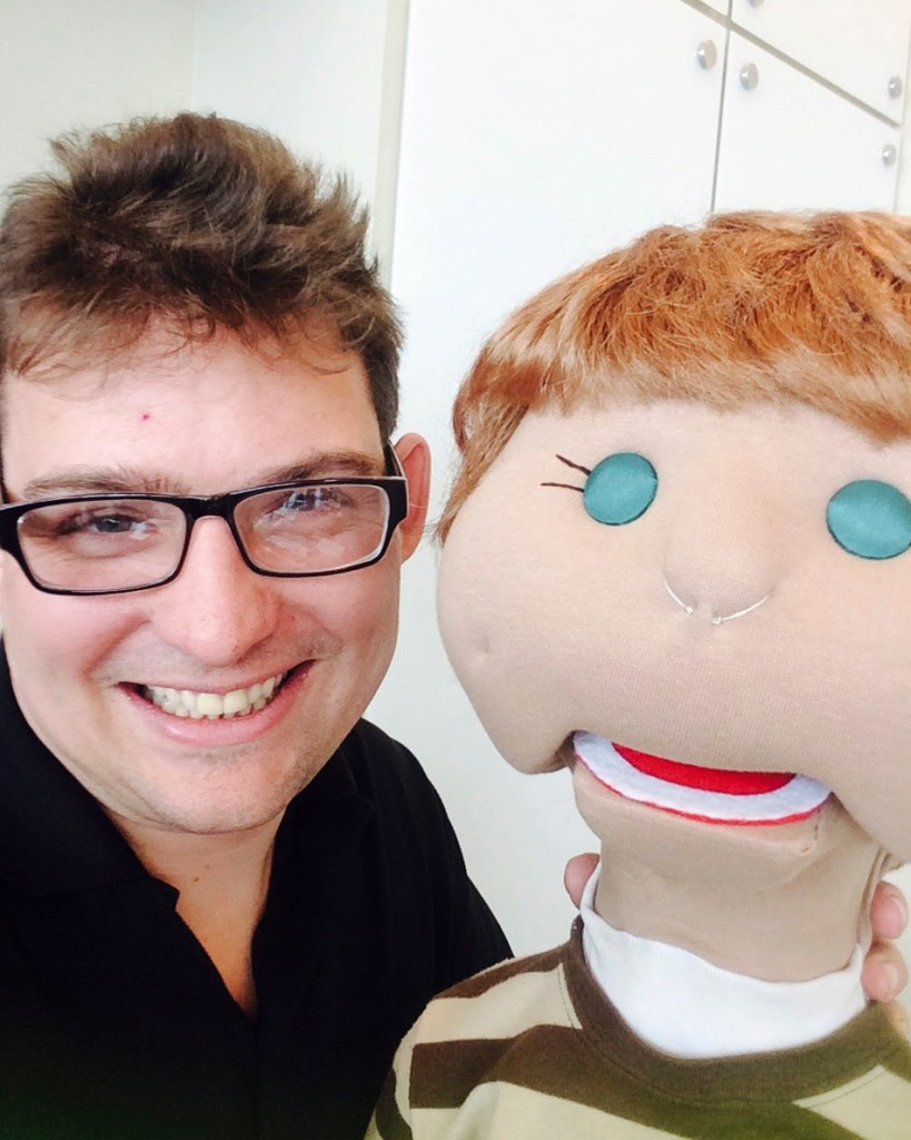A smiling man holding one of the Include Me puppets
