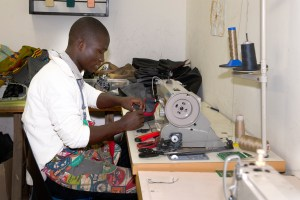 Young man at sewing machine making car tyre tube bags