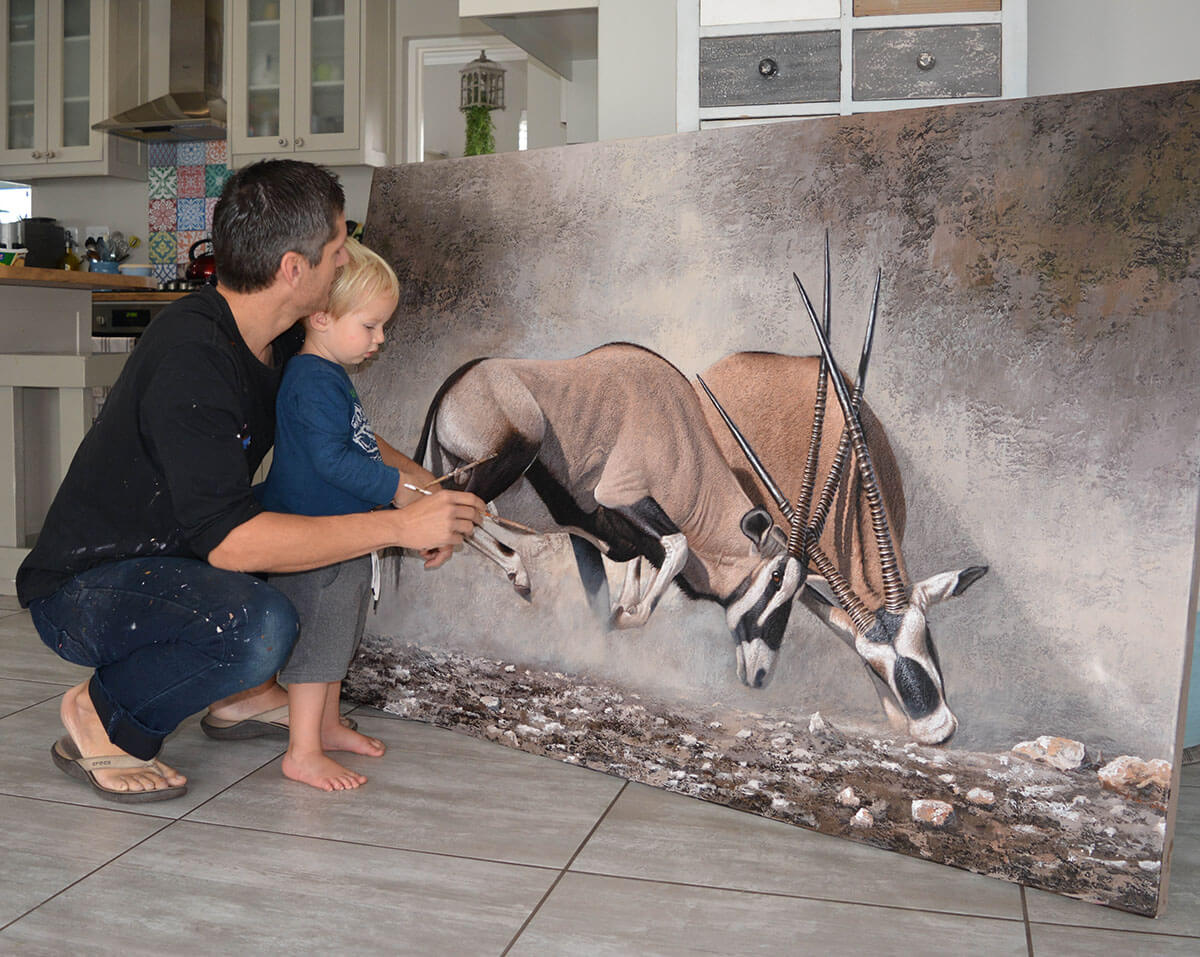 Danie Marais with his son Luka and the painting Clashing of horns