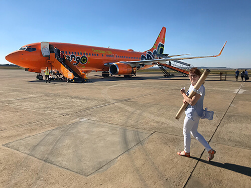 Xandra Frambach from Nwabisa African Art Boarding a flight in South Africa holding painting