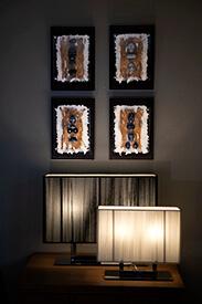 Decoratieve kunst met vier Kiezelsteen figuur stukken op wand boven schemerlamp