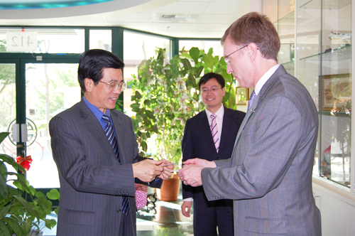 Attorney General Rob McKenna (right) exchanges business cards with Chinese Consul General of San Francisco Gao Zhansheng (left) as his secretary (center) looks on in the lobby of Northwest Asian Weekly's office on Sept. 24. (Photo by George Liu/NWAW)