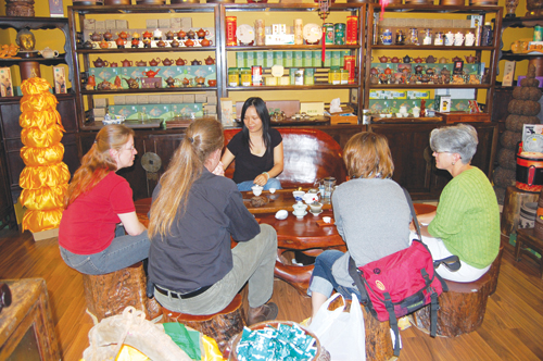 Dafe Chen's wife, Grace Li, demonstrates how to properly prepare tea to an eager group of people.