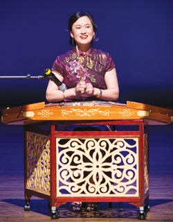 Buyun Zhao smiles at the crowd from behind the yangqin, a classical Chinese instrument.