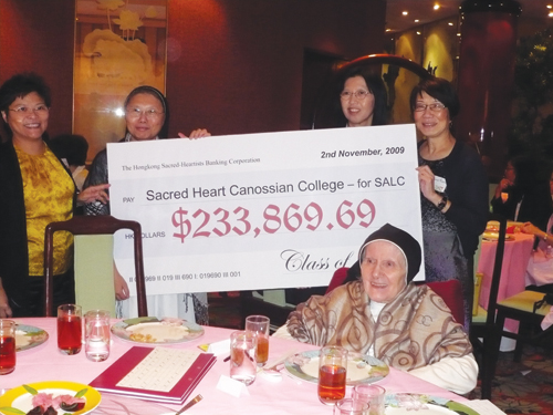 Assunta Ng's former high school principal, Mother Ida, now retired, sits in front of a check that equates to about $30,000 USD raised by Sacred Heart Canossian College (SHCC) alumni. In the back behind the check are (from left): Maria Law, Sr. Agnes Law, University of Washington alumnus Agnes Kwan, who graduated from the UW in 1982 with a degree in computer science, and Alice Chan. (Photo by Assunta Ng/NWAW)