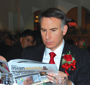 Dow Constantine reads an issue of Northwest Asian Weekly at the Top Contributors dinner on Dec. 4