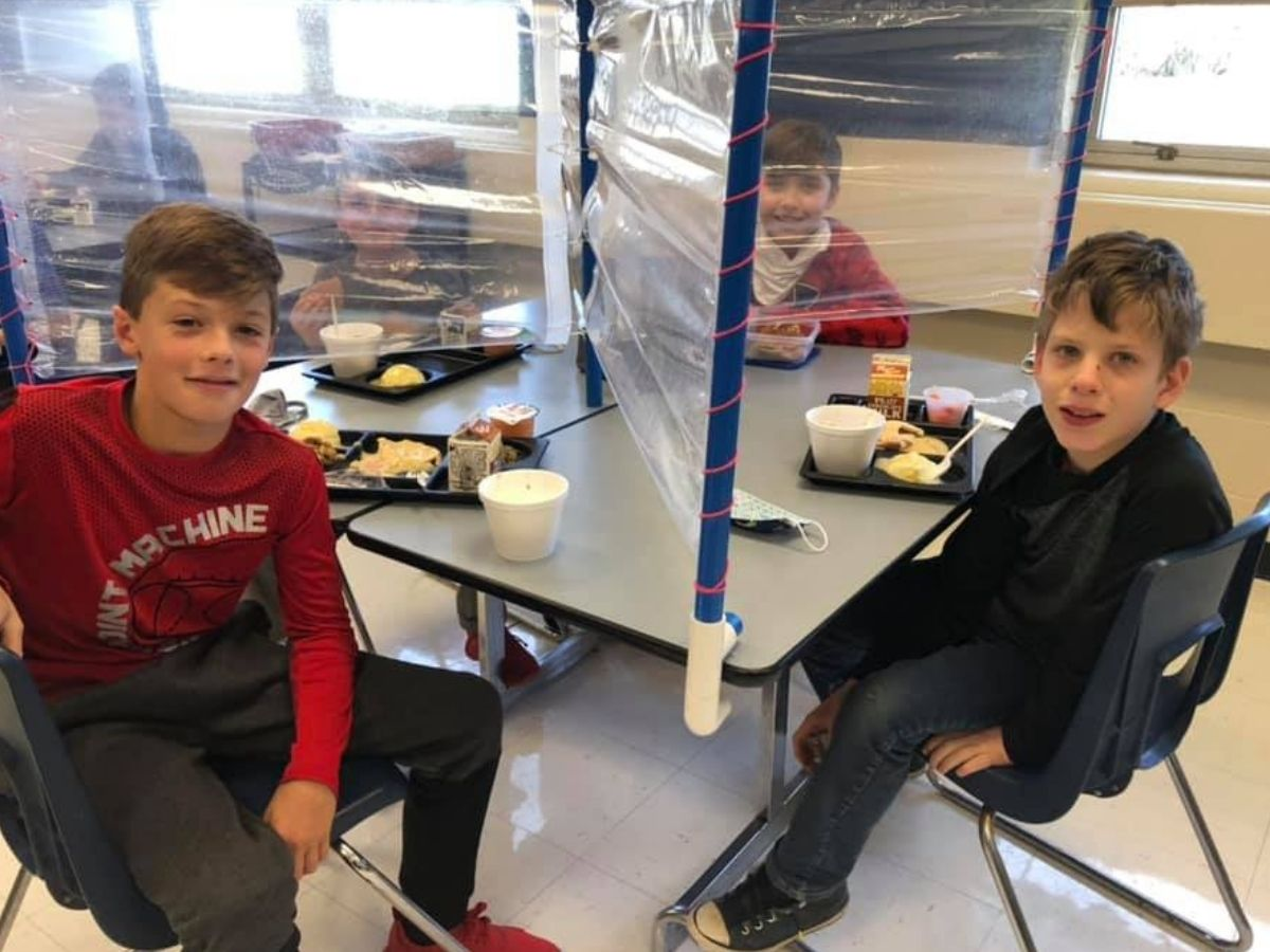 students sitting at lunch table with divider