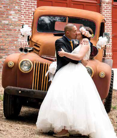 Bride and groom kissing in front of old truck.