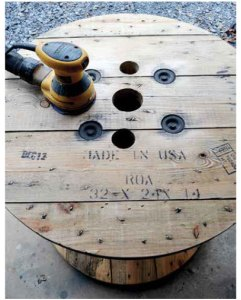 Wooden spool table with sander on top.