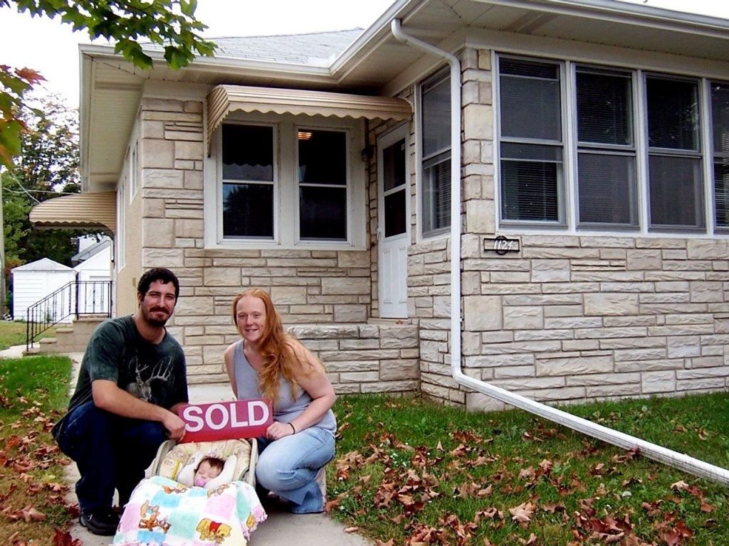 """A couple and their baby hold a """"sold"""" sign in front of their new home."""