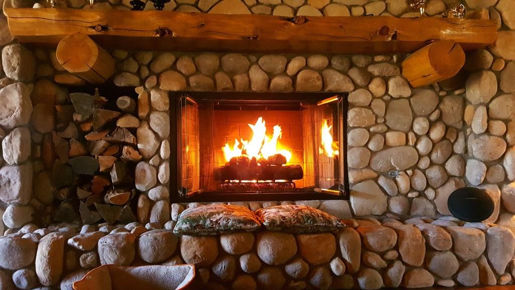 A fire burns in a fieldstone fireplace.
