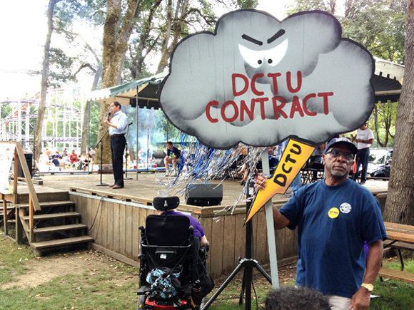 City of Portland Commissioner Dan Saltzman (on stage) announced at the Labor Day picnic that he'll run for re-election. But as symbolized by the sign held by union retiree Willard Valentine, there's a cloud hanging over his relationship with organized labor: A City push to make it easier to outsource workers, in bargaining with the seven-union 1,600 employee coalition known as DCTU.