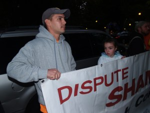 """Sean Carter, joined by his 11-year-old daughter Kylee and two co-workers, stands outside a $125-a-plate fundraiser with a banner reading """"Shame on Walsh Construction."""""""