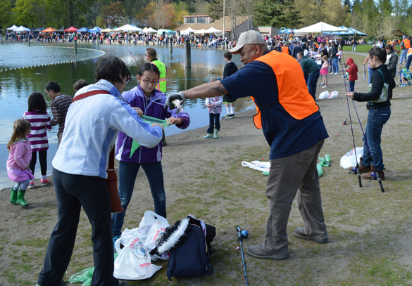 """Volunteer Ronnie Jimmerson helps a girl and her mother bag a trout at Klineline Pond in Vancouver.  Several dozen union members from IBEWLocal 48, Sheet Metal Workers Local 16 and Laborers Local 296 volunteered on Saturday, April 12. """"I come out because I get a kick out of it,"""" Jimmerson said. Jimmerson just started fishing a few years ago — and he loves it."""
