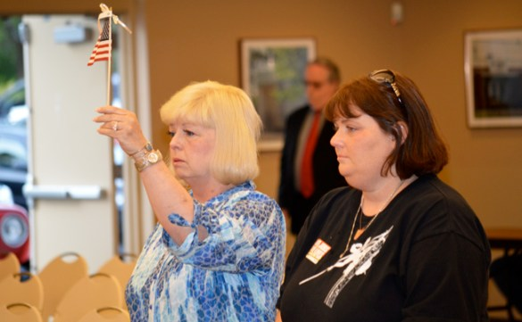 At an April 28 Workers Memorial Day ceremony in Portland, Claudia Cook-Winkler (left) holds up a flag as the name of her son Benjamin Cool is read. Next to her is Benjamin's sister, Anna Cool-MacRae.