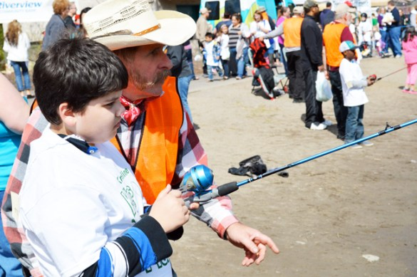 JR Robertson advises a boy on the art of fishing.  A few minutes later they landed a nice rainbow trout.
