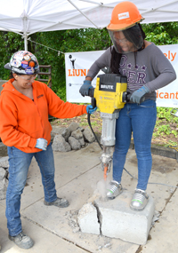 A popular booth at the fair lets participants operate a jack-hammer. Helping out is Laborers Apprenticeship Coordinator Aida Aranda, a member of Laborers Local 296. She has volunteered to help at the fair for the last five years.