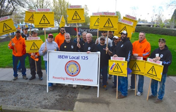 Members of IBEW Local 125 walk an information picket outside PacifiCorp headquarters in Northeast Portland. PacifiCorp is the parent company of Pacific Power, where IBEW is trying to secure a new contract.