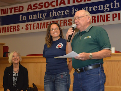 Retiree chapter president Dave Stahly, at the mike, with Tori Geter and guest trainer Judy Zehr.