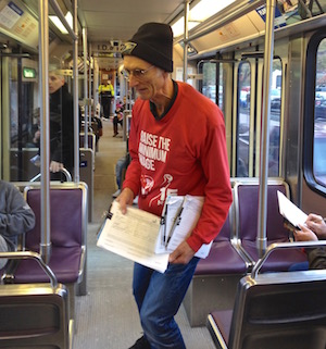 Retired letter carrier Jamie Partridge, above collecting signatures on TriMet light rail Blue Line, is the chief petitioner on a ballot measure to raise Oregon's minimum wage to $15 an hour by 2018.