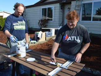 ATU Local 757 member Linda Jauron-Mills, a Trimet bus operator, paints shutters with her son Bob Jauron.