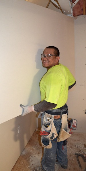 Manny Rodriguez of Performance Contracting (PCI) hangs drywall in a new classroom at the Regional Training Center in Northeast Portland.