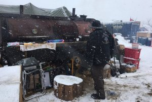 SMOKER DUTY: ILWU Local 4 member Steve Hunt tends to a meat smoker at the Standing Rock protest camp. (Photo via the Twitter feed of Guardian reporter Julia Carrie Wong)