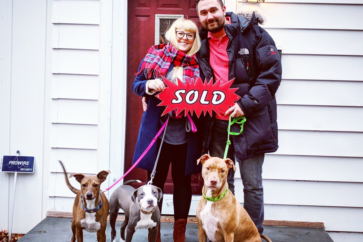 Couple with dogs holding sold sign