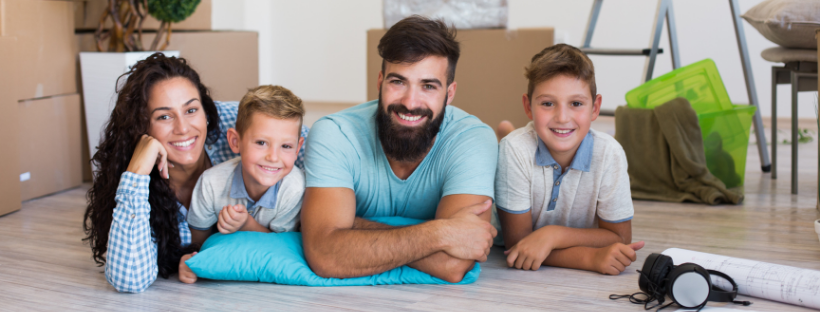 Family surrounded by moving boxes