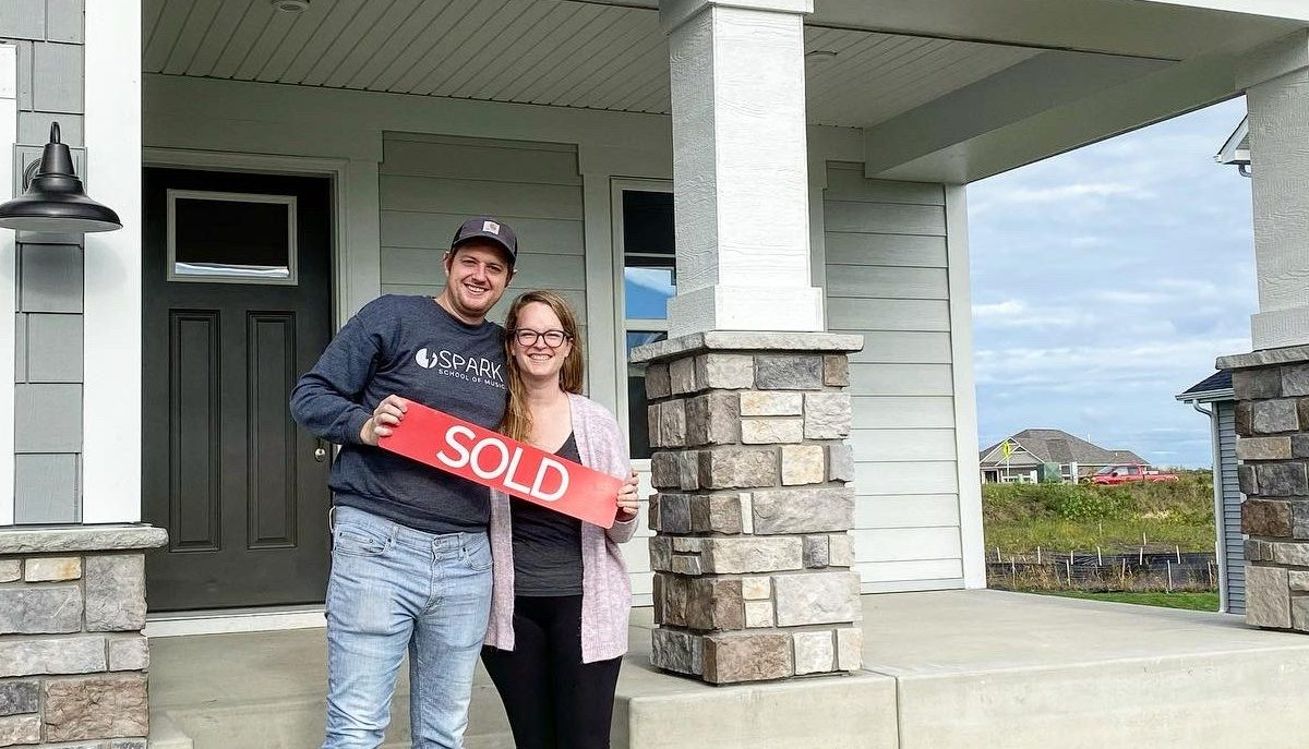 Couple holding sold sign in front of home