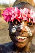 Ethiopia: Omo River Basin: Lebuk, a Karo village, portrait of a woman wearing a chain of desert rose blooms on her head