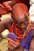 Kenya: Amboseli, Maasai (aka Masai) groom Saroni ole Nkaja applying ochre for the wedding ceremony, May.