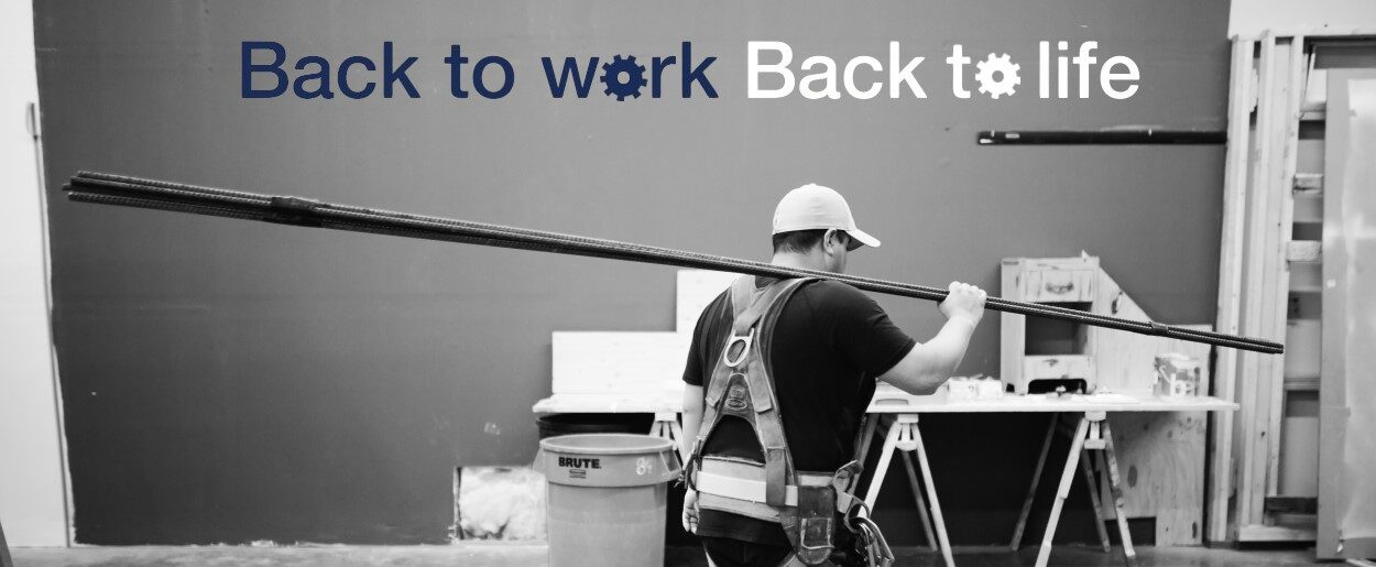 "Black and white photo of man carrying long piece of iron rebar with company slogan ""Back to work, back to life"" above him."
