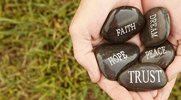 Hands holding stones with inspirational words