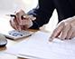 A man's hands using a calculator to prepare a bill
