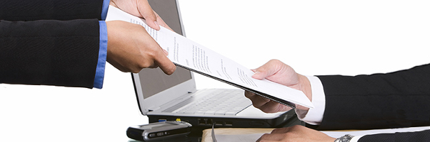 A process server hands a document to a businessman.