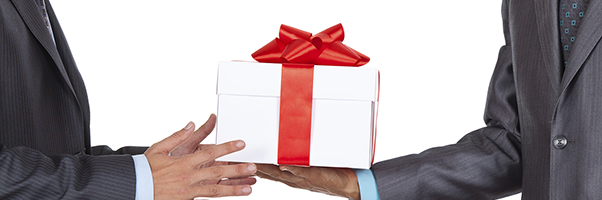 Two men in suits exchanging a gift.