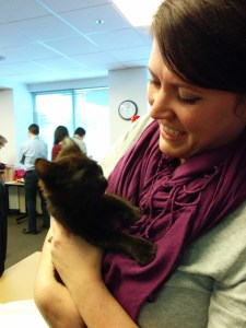 A woman holding a black kitten