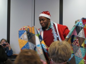Phillip Bryant wearing a santa hat and holding a quilty