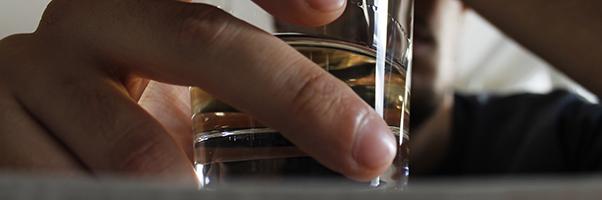 Drunk guy holding a shot of whiskey.