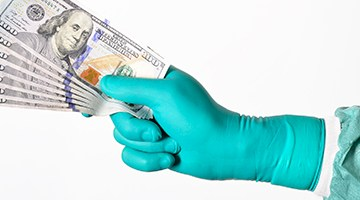 A gloved surgeon hand holding C-notes.