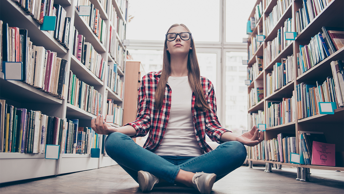 Woman meditates in library