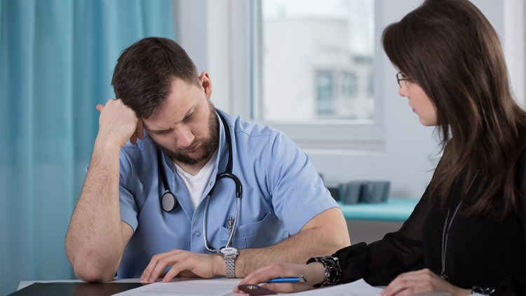 A doctor reviews a document with his lawyer.