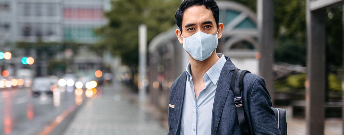 Lawyer with takeaway coffee and flu mask on city street