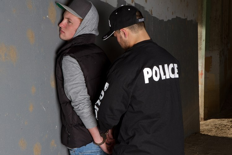 Police officer handcuffing a teenage boy.
